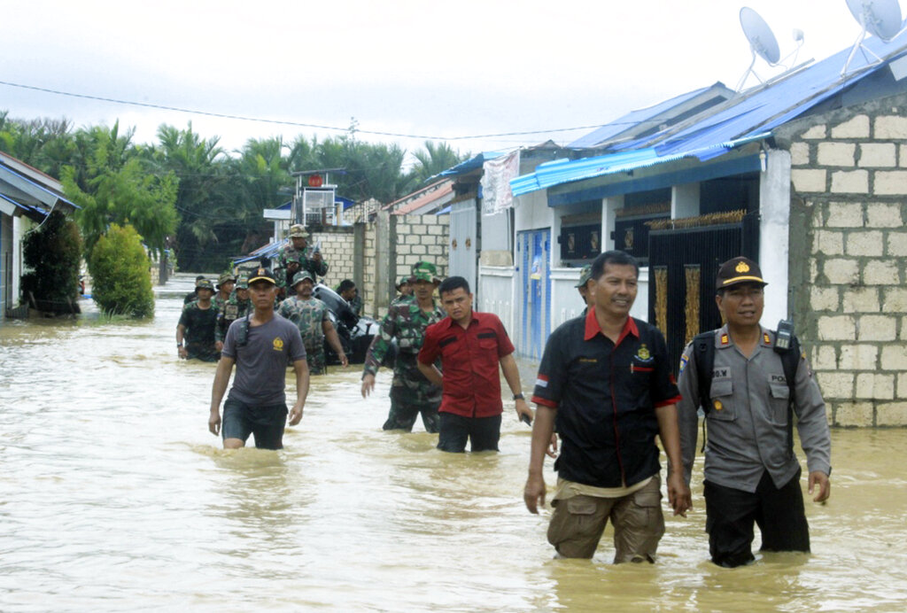 Indonesian police and soldiers search for residents who need assistance at a flooded neighbourhood in Sentani, Papua Province, Indonesia, on Monday.