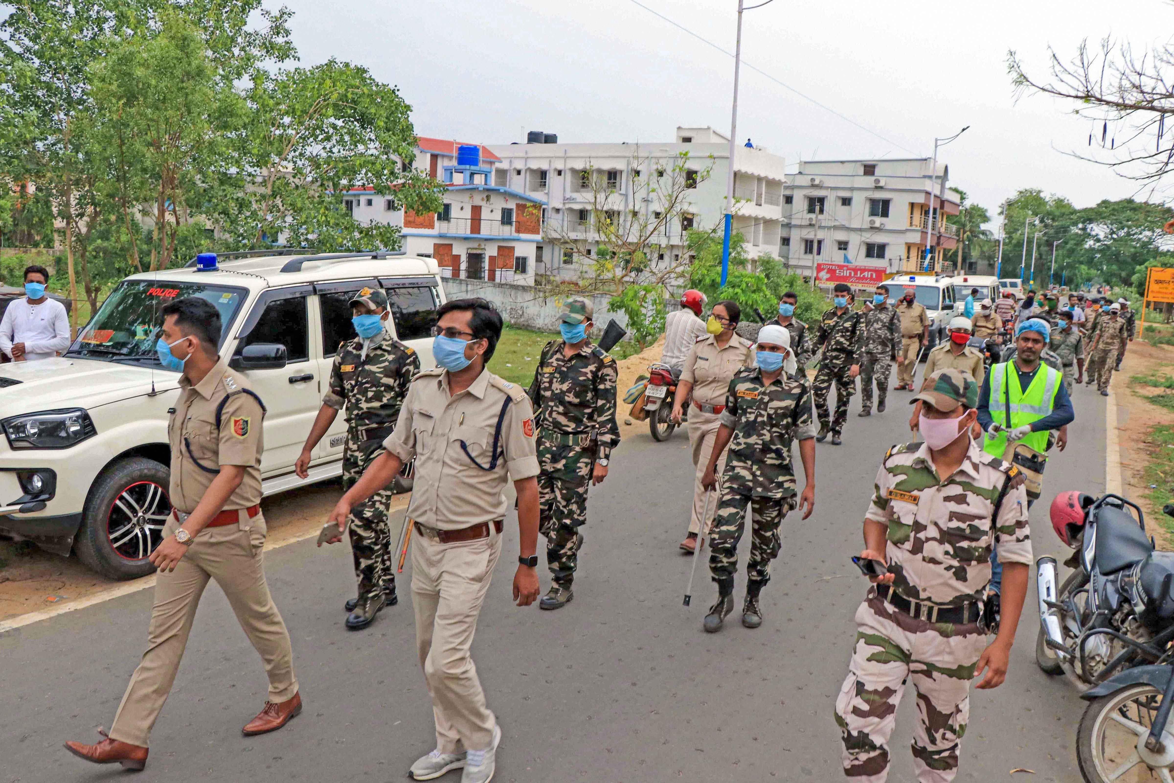 Security forces personnel try to control the situation after a protest by the residents of Goalpara village against setting up of a quarantine centre for COVID-19 suspects in their village, in Birbhum district, Friday, May 1, 2020.