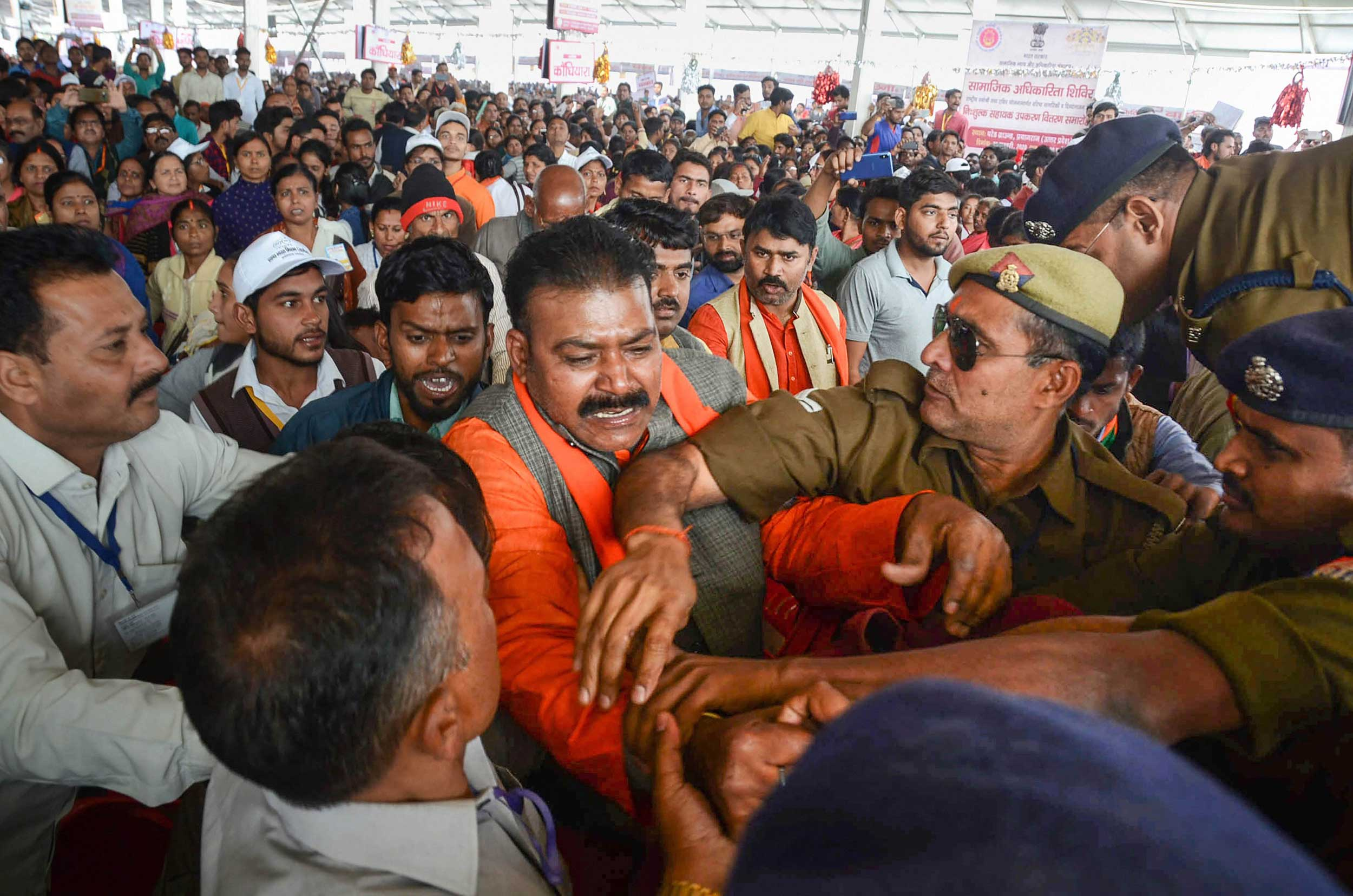 BJP workers tussle with protesters during a programme to distribute equipment such as tricycles, hearing aids and electronic walking sticks among the differently-abled and the aged, at the Parade Ground in Allahabad, on Saturday.