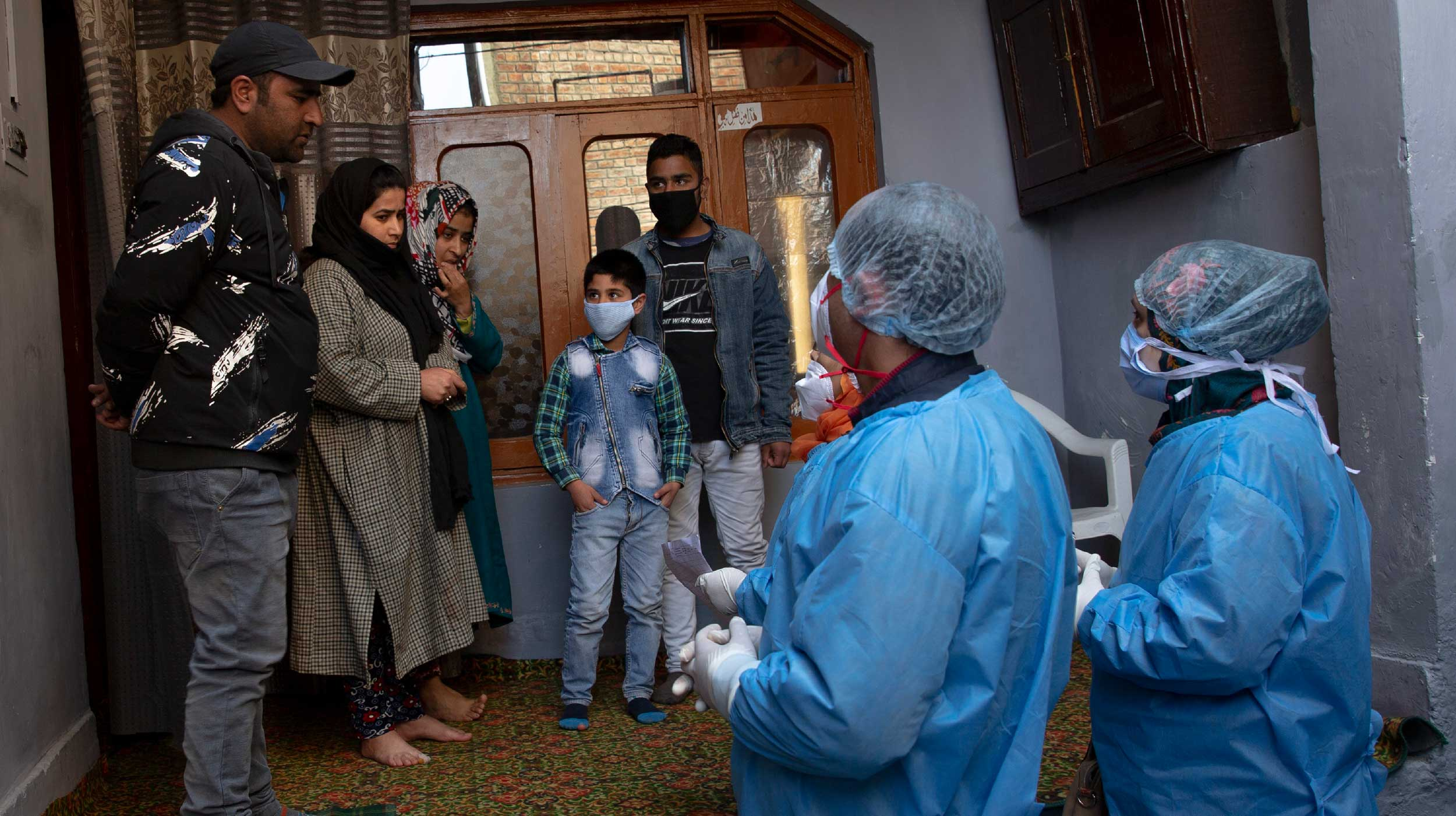 Medical workers talk to residents during the door to door campaign to check any possible contact with the woman, who tested positive to the coronavirus after recently arriving from Saudi Arabia, in Srinagar on Thursday.