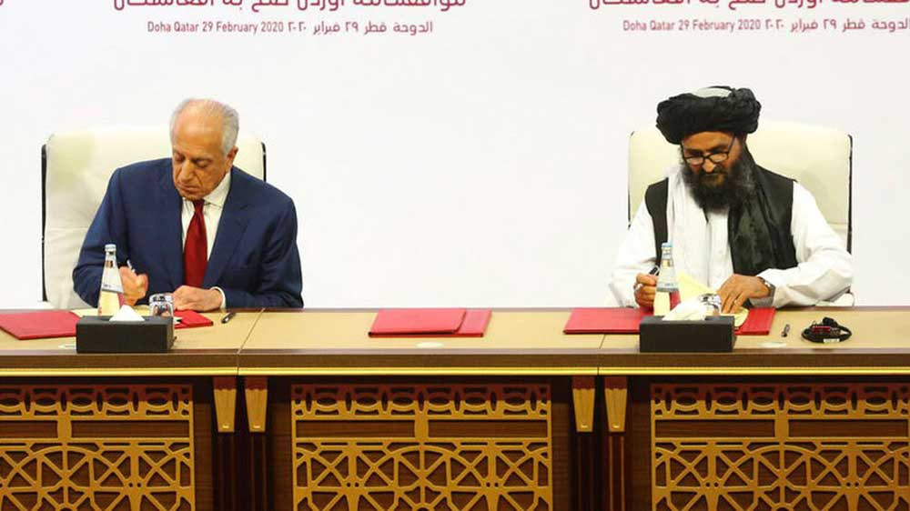 US peace envoy Zalmay Khalilzad and Mullah Abdul Ghani Baradar, the Taliban group's top political leader, sign the peace agreement in Doha