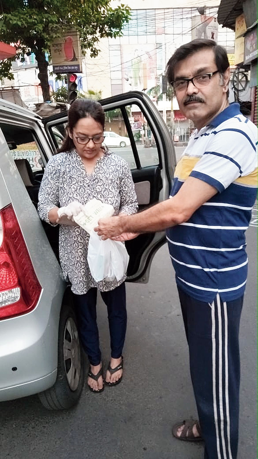 Sarbajit Ghatak from the batch of 1983, who owns a medicine shop, handing over a consignment to Pointer volunteer Nivedita Roy Burman on Saturday.