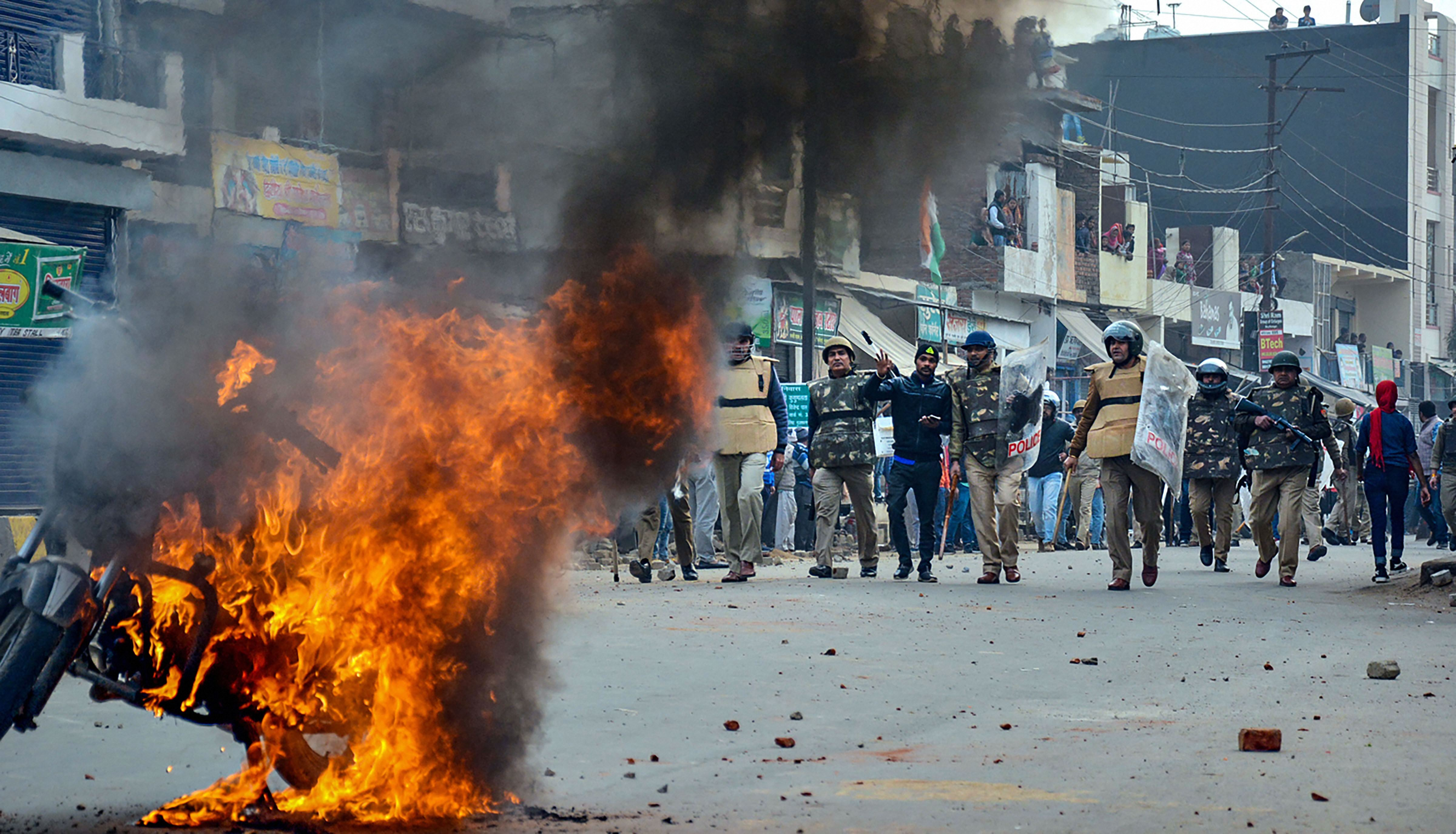 Smoke rises out of a burning vehicle during a protest against the Citizenship (Amendment) Act, in Muzaffarnagar, Friday, Dec. 20, 2019.