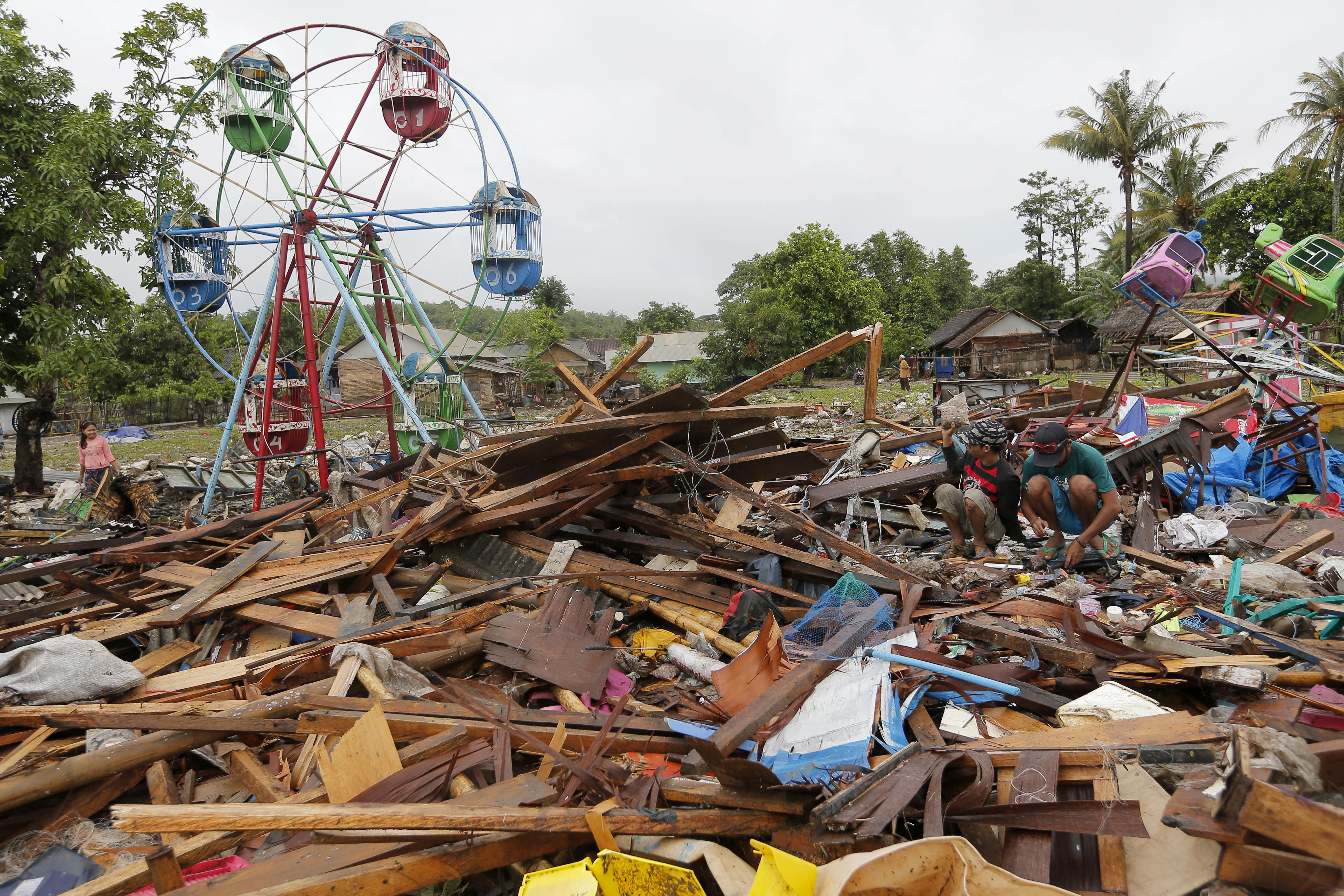 People collect usable items in debris after Saturday's tsunami in Sumur, Indonesia, on Christmas Day.