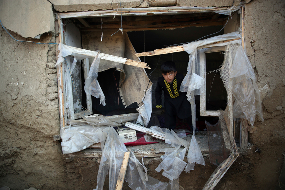 A boy inspects his damaged home after after an attack near the Bagram Air Base in Kabul on December 11