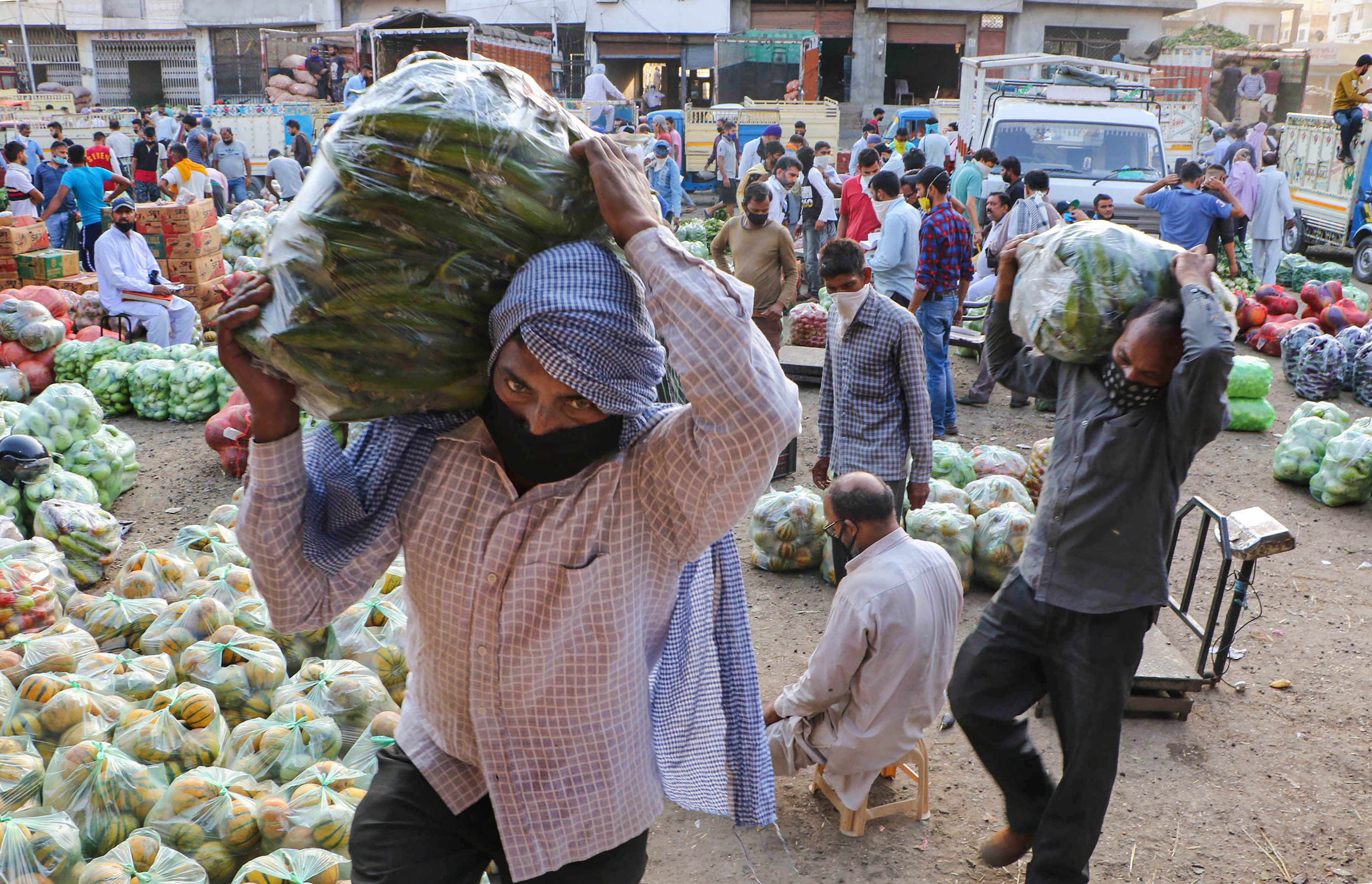 Vendors carry vegetables at a wholesale vegetables market, during ongoing COVID-19 lockdown, in Jammu, Monday, June 15, 2020.