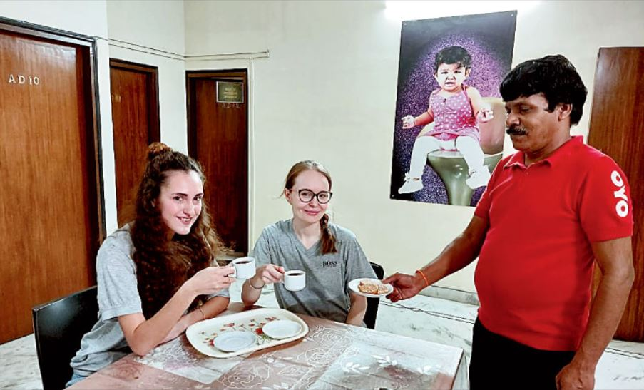 Veronika Migel and Maya Danileva are served biscuits by the staff of AD Block's Next Generation Guest House