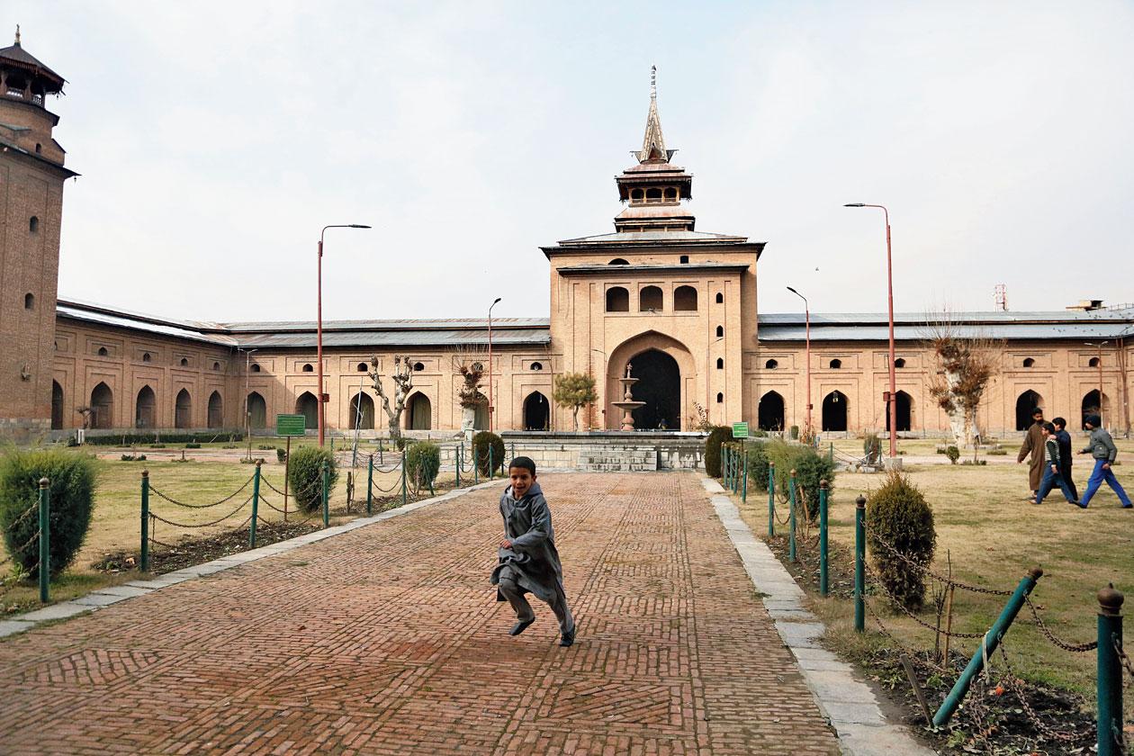 A boy plays outside Jamia Masjid in Srinagar.