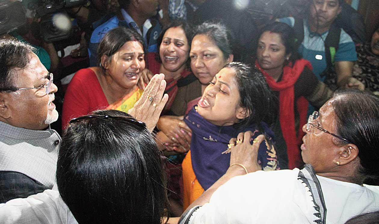 Partha Chatterjee speaks to Satyajit Biswas's wife (right).