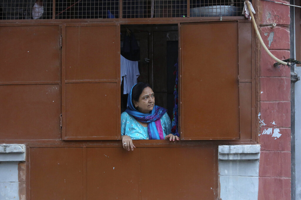 In this August 23, 2019, photo, a Kashmiri Hindu woman looks from inside her house at the Jagti migrant camp in Jammu