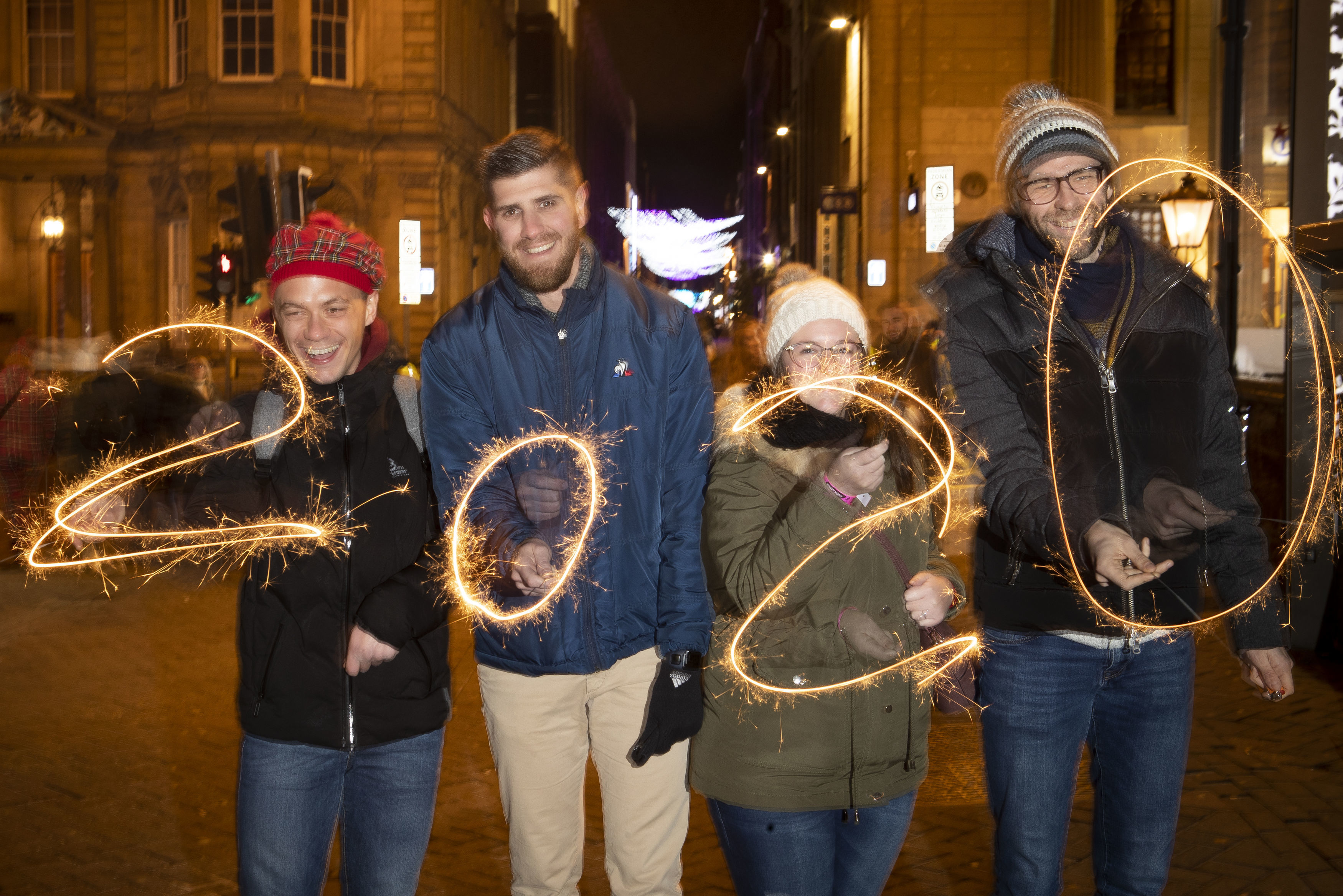 French tourists pose together with fireworks to make the sign of the New Year, left to right, Alexandre Levy, Johann Lemarquand, Rachel Ferrier and Benoit Jaouen, from Cherbourg, France, during the Hogmanay New Year celebrations in Edinburgh, Scotland, on December 31, 2019