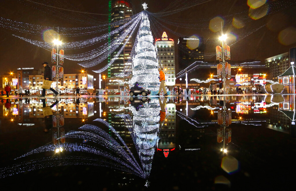A New Year tree is reflected in a pond as people walk on the square in Minsk, Belarus, on December 26