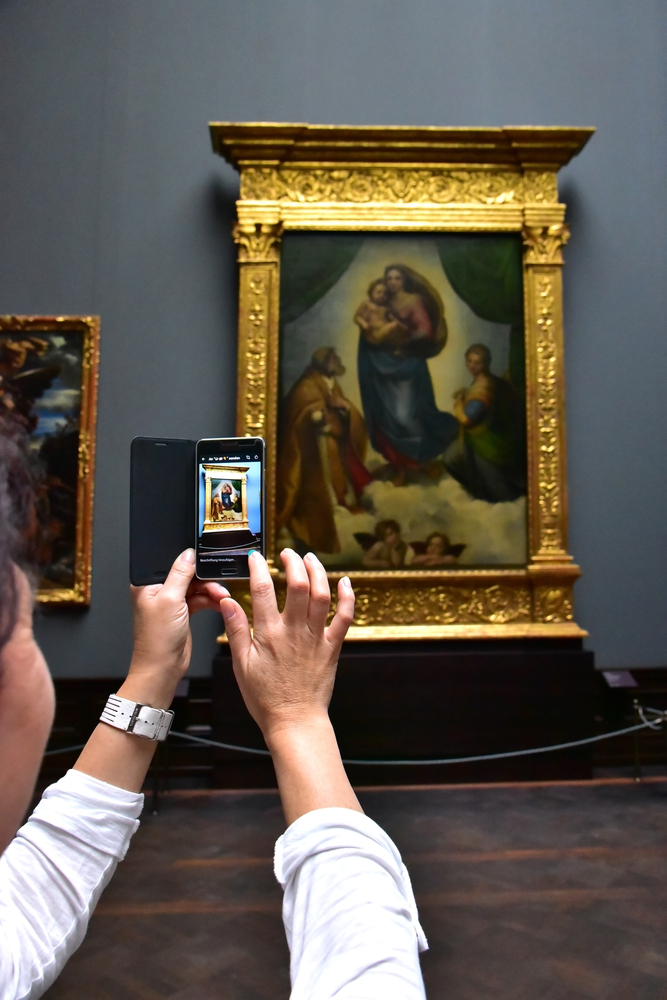 A tourist takes a photo of Raphael's Sistine Madonna in Zwinger, Dresden, Germany