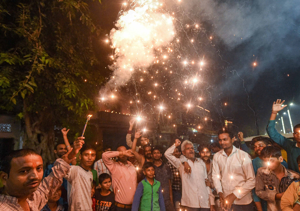 Residents of Sadatganj area burst fire crackers outside their houses to celebrate Supreme Court's judgment, in Ayodhya, Saturday, November 9, 2019.