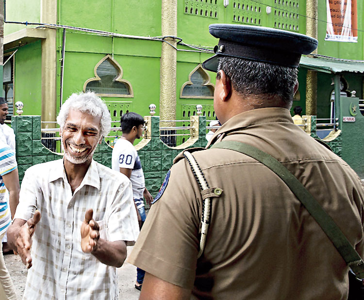 A Muslim man reaches out to shake hands with policemen standing guard during Friday prayers in Colombo
