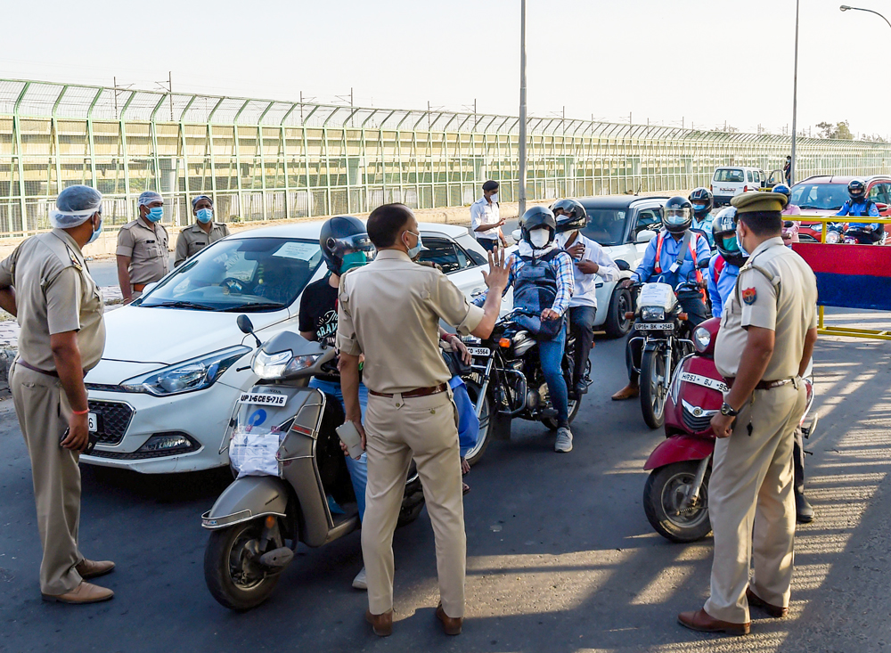 Security personnel stop commuters for checking before entering in Noida during the nationwide complete lockdown, at Okhla barrage in New Delhi, Wednesday, April 22, 2020.