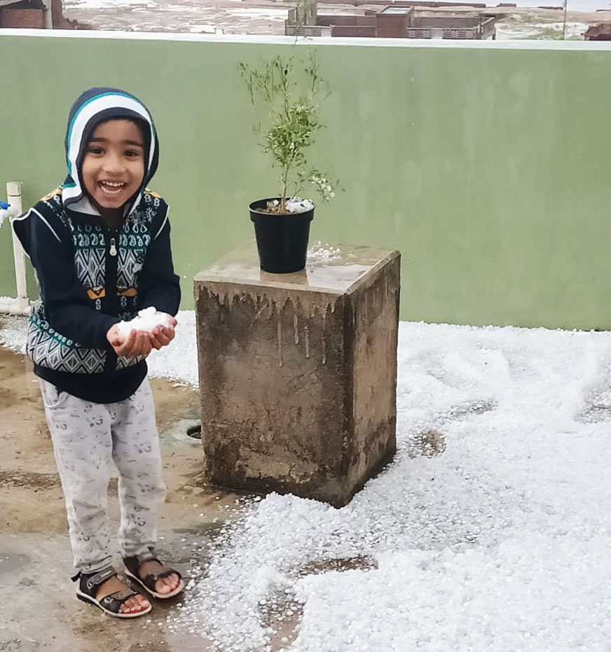 A kid with a handful of hailstones near Chainpur in Palamau on Tuesday