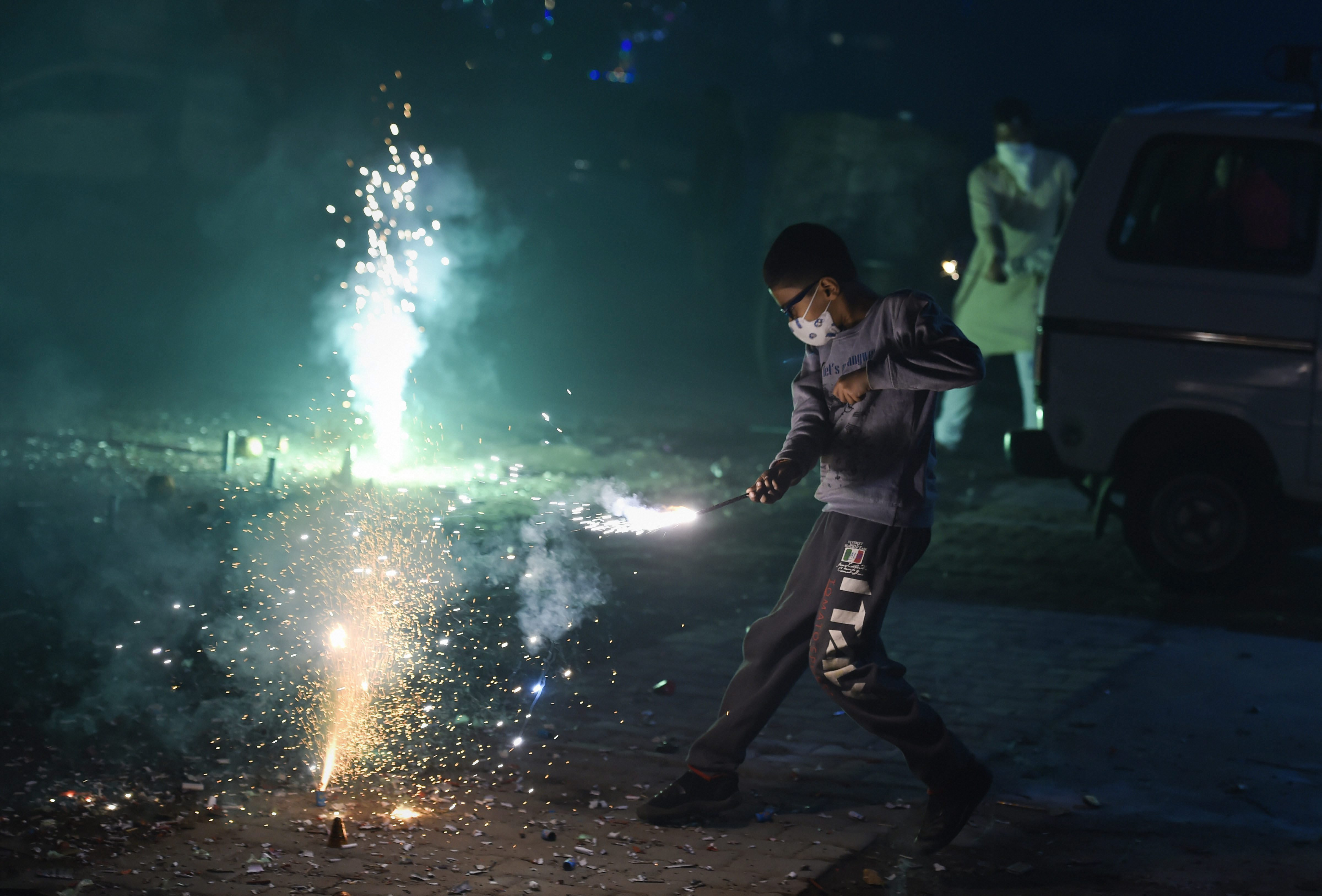 A child wearing an anti-pollution mask lights firecrackers in New Delhi to celebrate Diwali on Wednesday, November 7. Officials said the city recorded its worst air quality of the year on the following morning due to firecrackers.