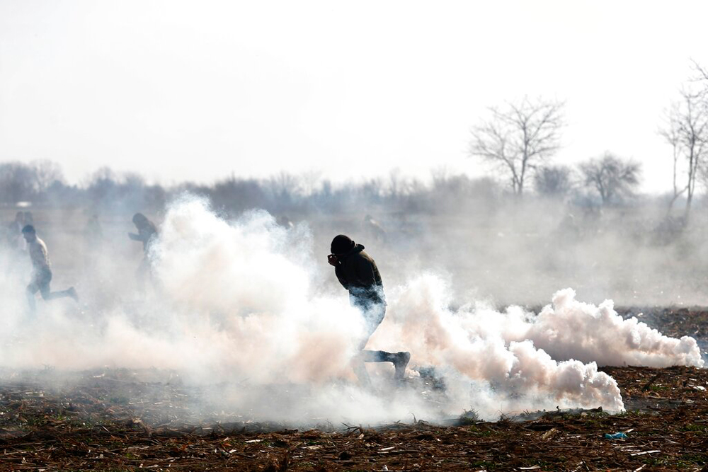 Migrants run to avoid tear gas thrown by Greek police during clashes in Edirne, at the Turkish-Greek border, on March 2