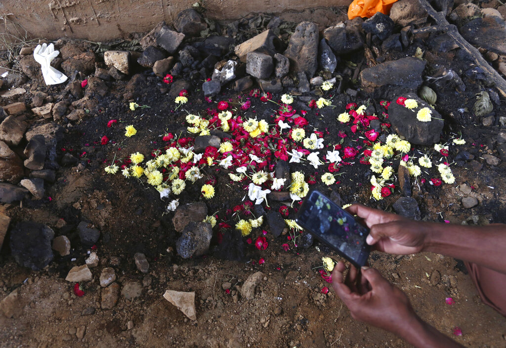 A man takes photos of the site where the burned body of a 27-year-old woman was found last week by a passer-by, in Shadnagar some 50 kilometers or 31 miles from Hyderabad, on Friday.