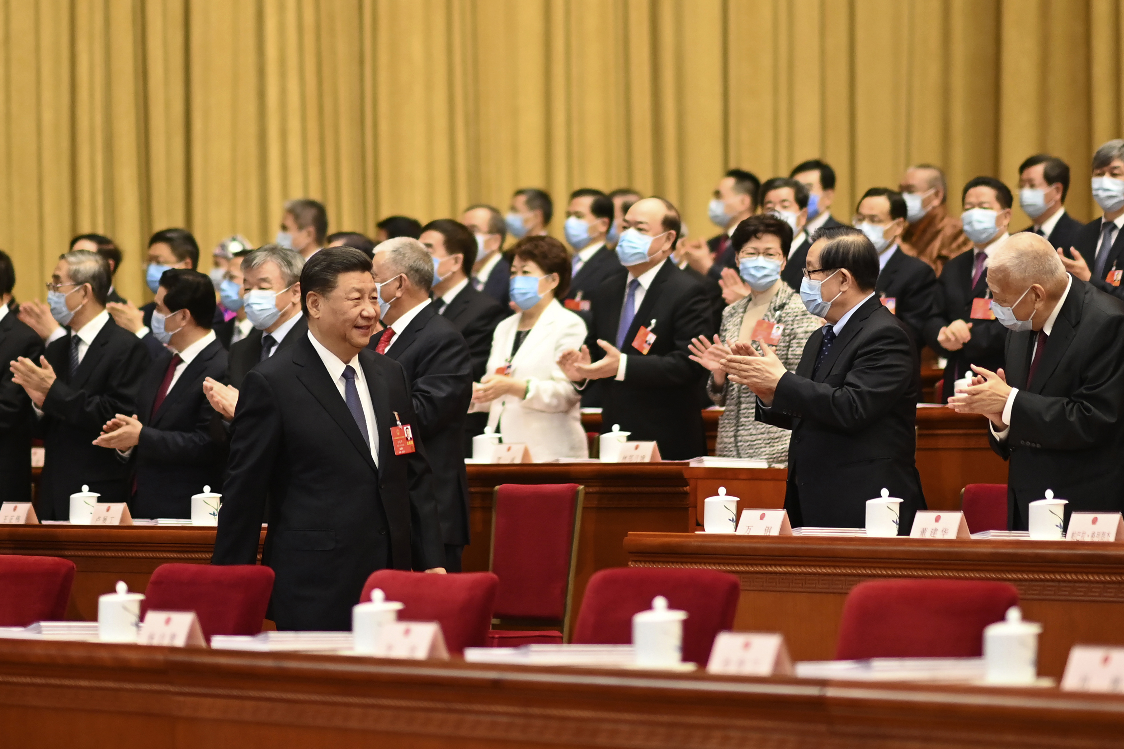 Chinese President Xi Jinping walks past ministers in  face masks during the opening session of the National People's Congress at the Great Hall of the People in Beijing on Friday.