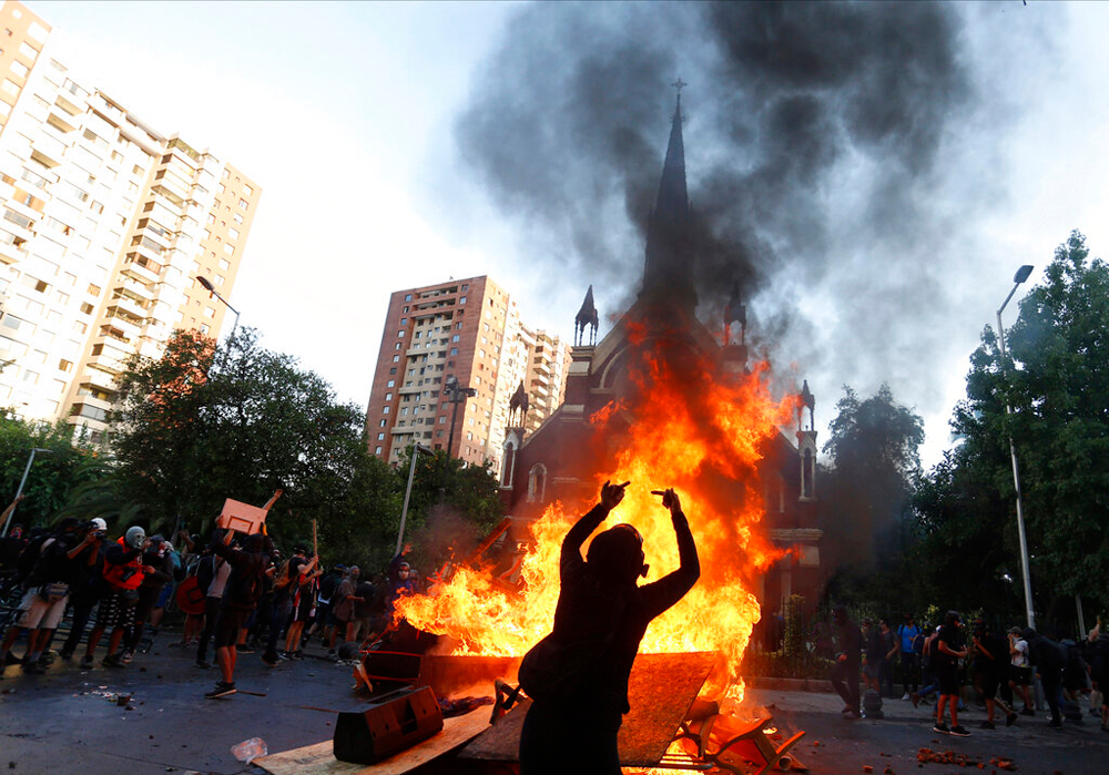 Anti-government demonstrators burn furniture from a Chilean police church during a protest in Santiago on January 3