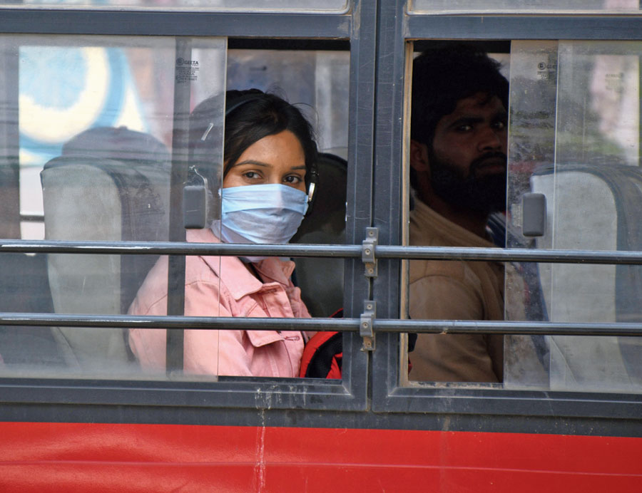 A woman with a face mask looks out of a bus window on Main Road in Ranchi on Saturday.