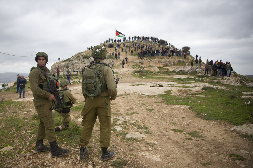 Israeli soldiers take position as Palestinian demonstrators gather during a protest against expansion of Israeli settlements, in the West Bank village of Beita near Nablus, on Monday, March 2