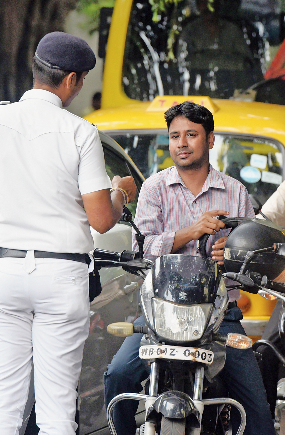 A policeman asks a biker to wear his helmet that was hanging from the handle of his motorcycle on Mayfair Road in Ballygunge on Friday