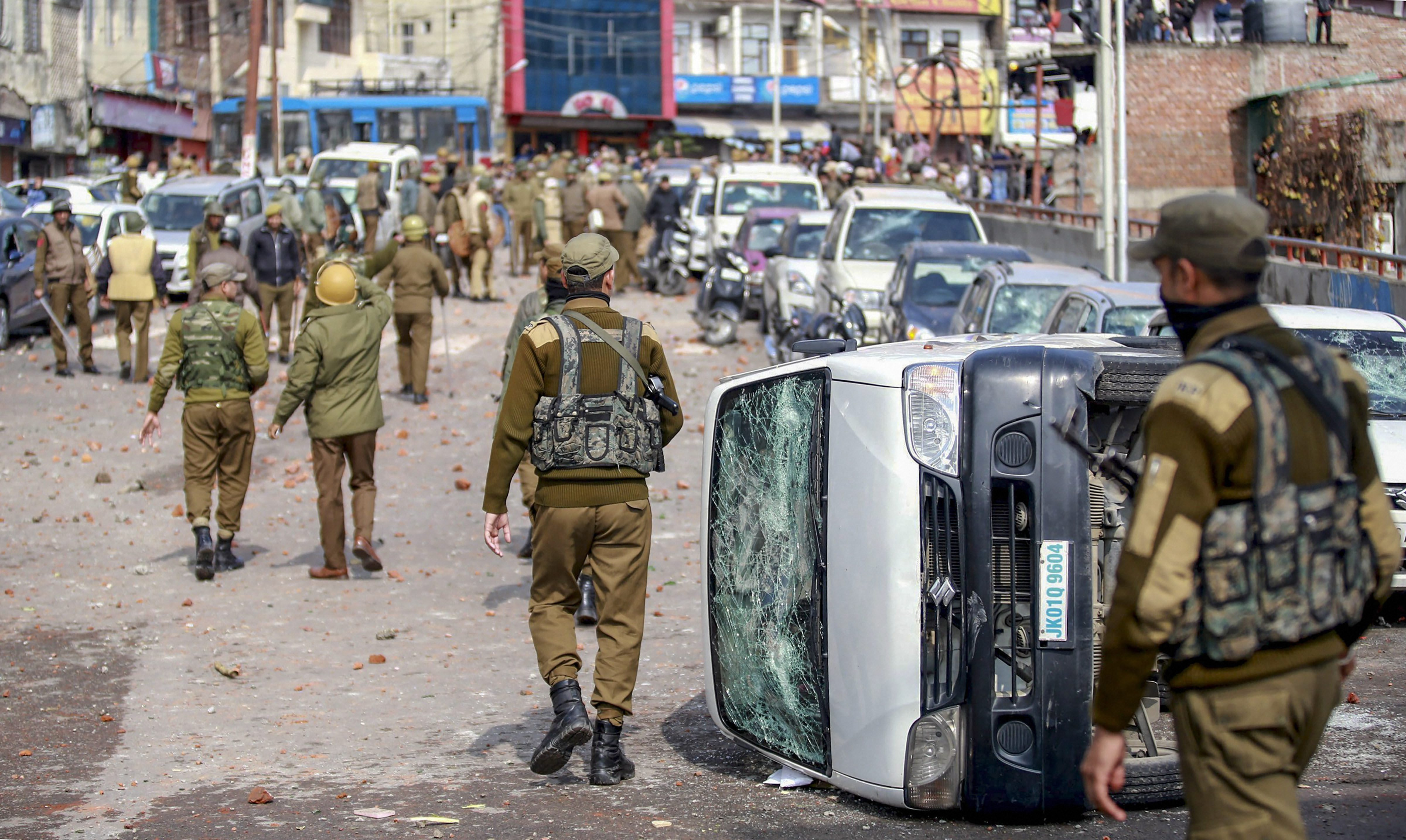 Security personnel patrol a street after people protesting against the Pulwama attack set fire to vehicles in Jammu on Friday.