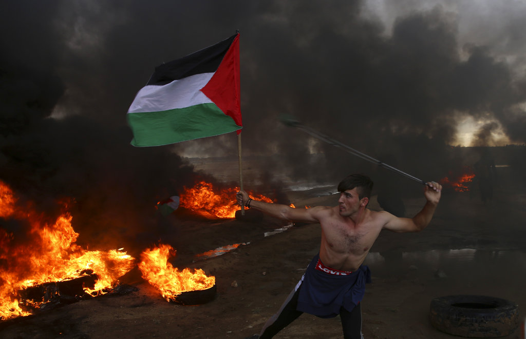 In this October 26, 2018, file photo, a protester hurls stones while holding the Palestinian flag amid burning tyres near the fence of the Gaza Strip border with Israel.