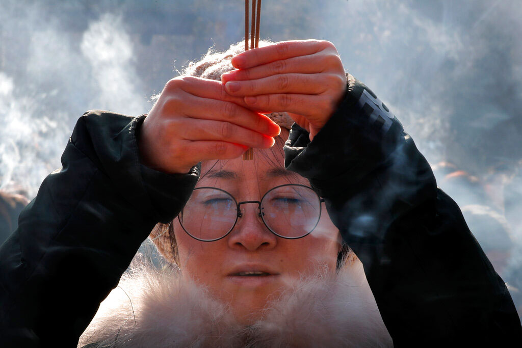 A woman holding incense sticks offers prayers on the first day of the New Year at Yonghegong Lama Temple in Beijing.