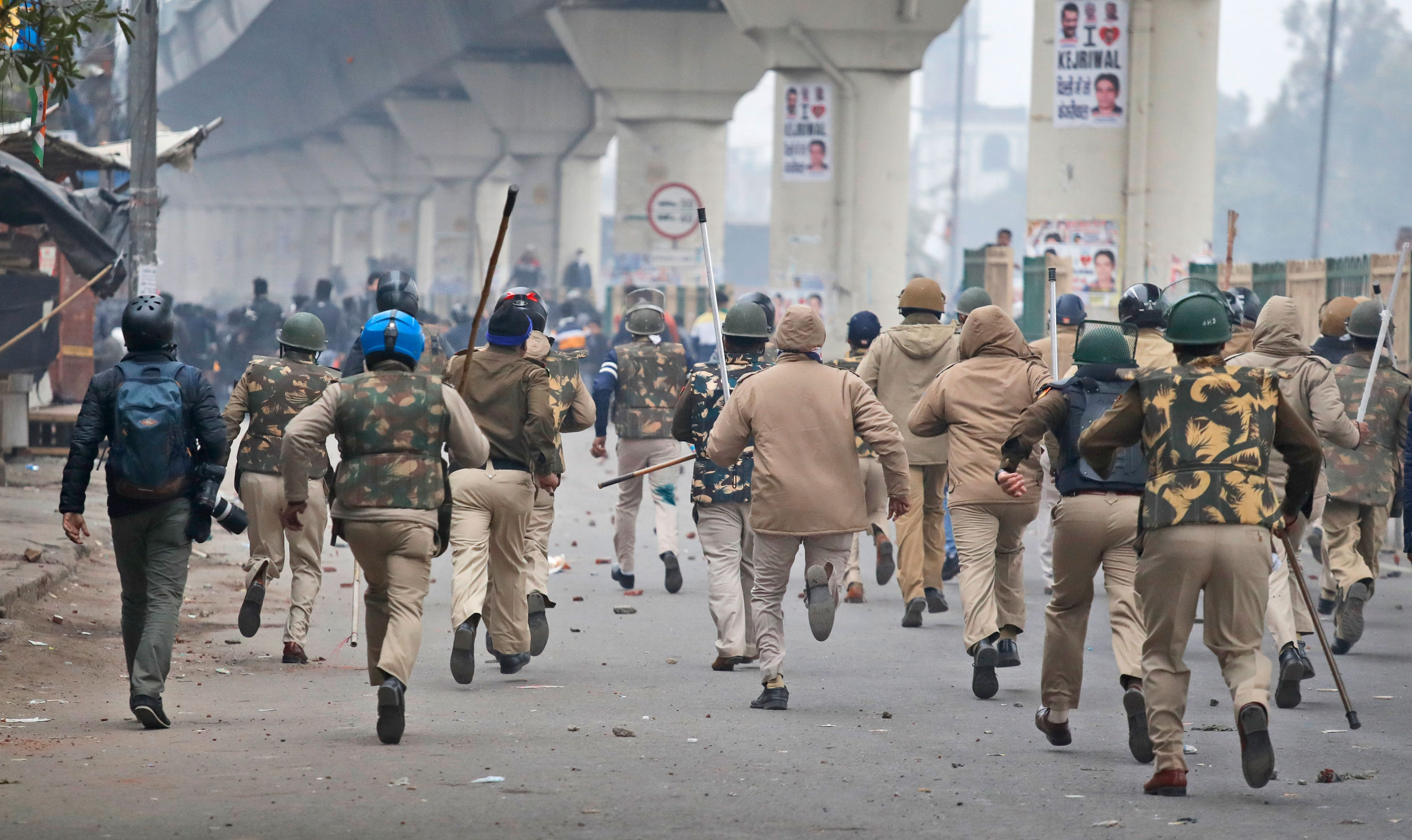 Policemen chase protesters during a protest against the new citizenship law in New Delhi on Tuesday.