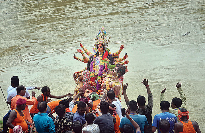 Devotees immerse an idol of goddess Durga in Dimapur on Tuesday.
