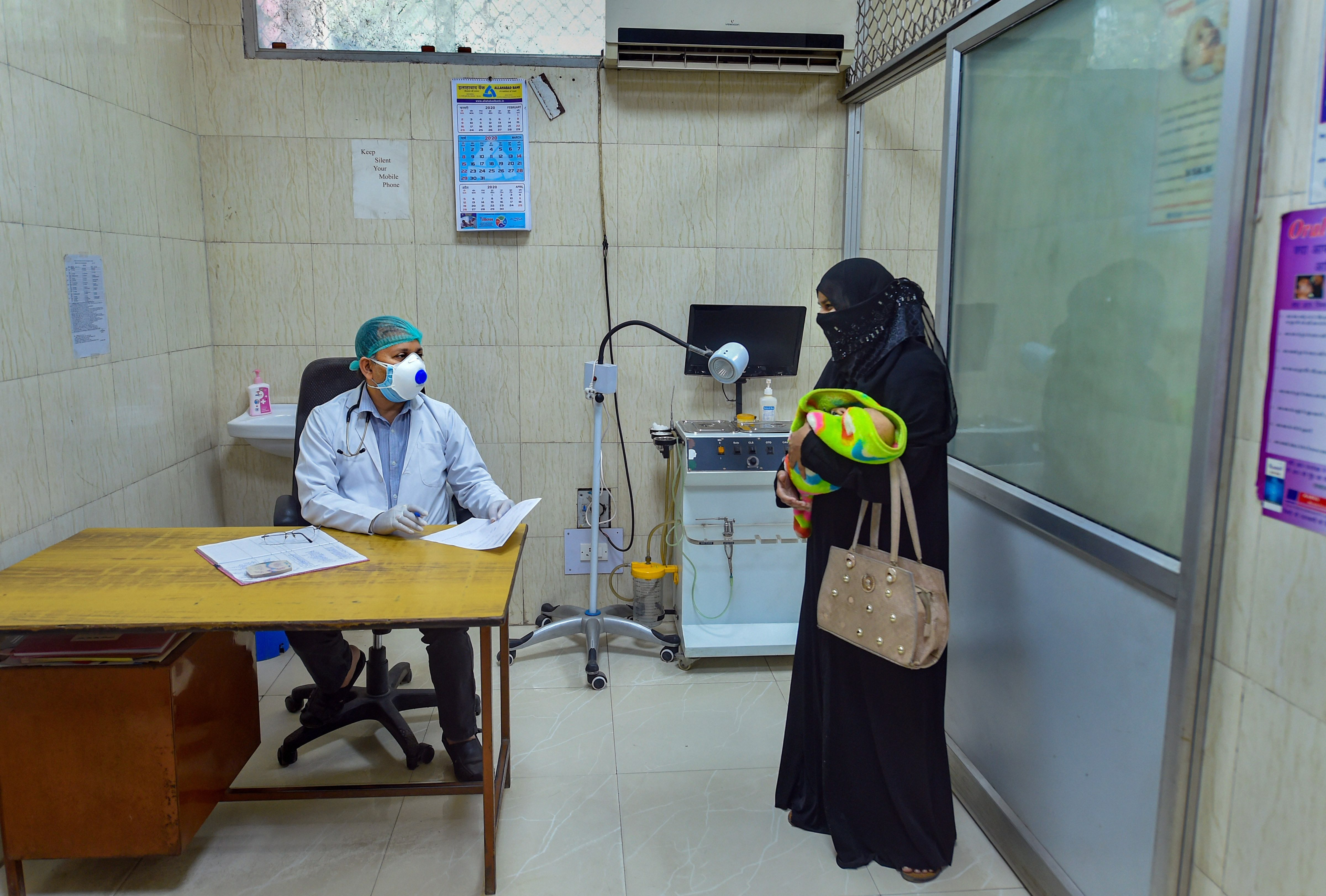 A doctor attends a patient in the Out Patients Departments (OPD) of a Civil Hospital as OPDs start functioning from today during the nationwide lockdown, in wake of the coronavirus pandemic, in Lucknow, Tuesday, April 21, 2020.