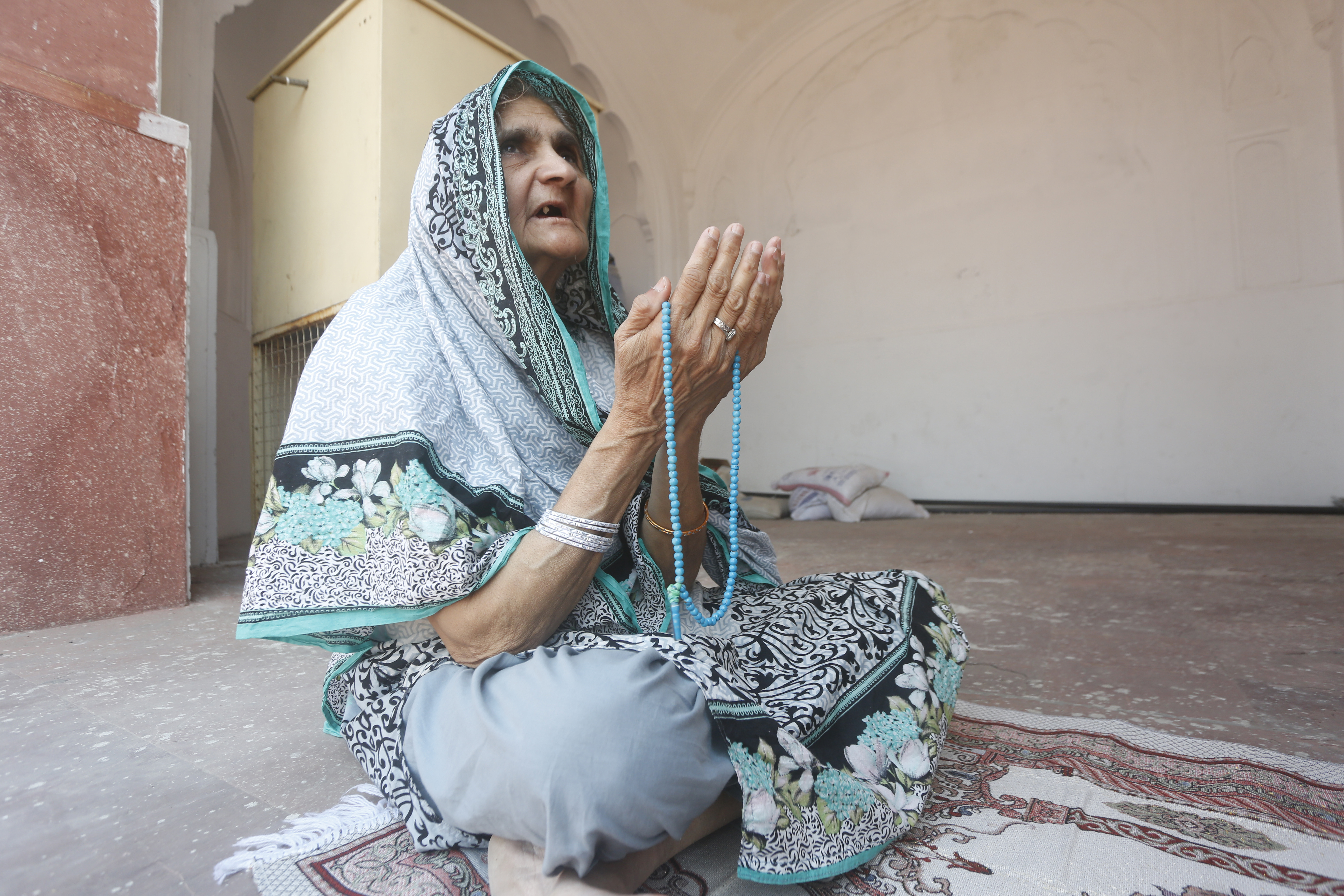 A woman attends Friday prayers at the Badshahi mosque during a government imposed nation wide lockdown to help avoid the spread of the coronavirus