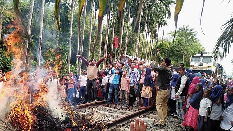 Protesters block a train in Karimganj on Tuesday