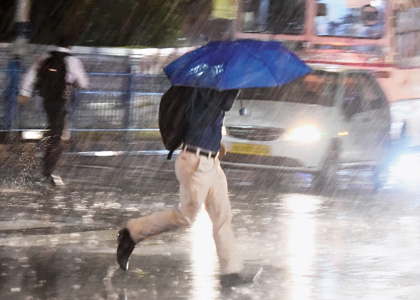 Pedestrians on Outram Road run for shelter during rain, which accompanied a squall, on Tuesday evening.
