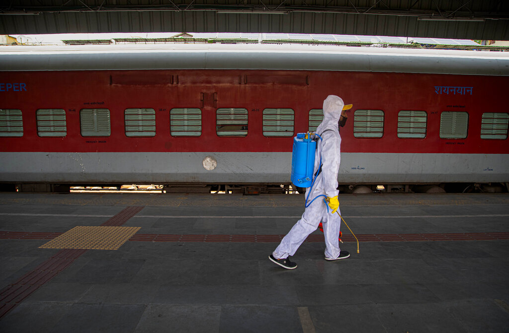 A railway worker walks to sanitize a train carrying migrant workers to their home states, at a railway station in Gauhati, India, Thursday, May 28, 2020.