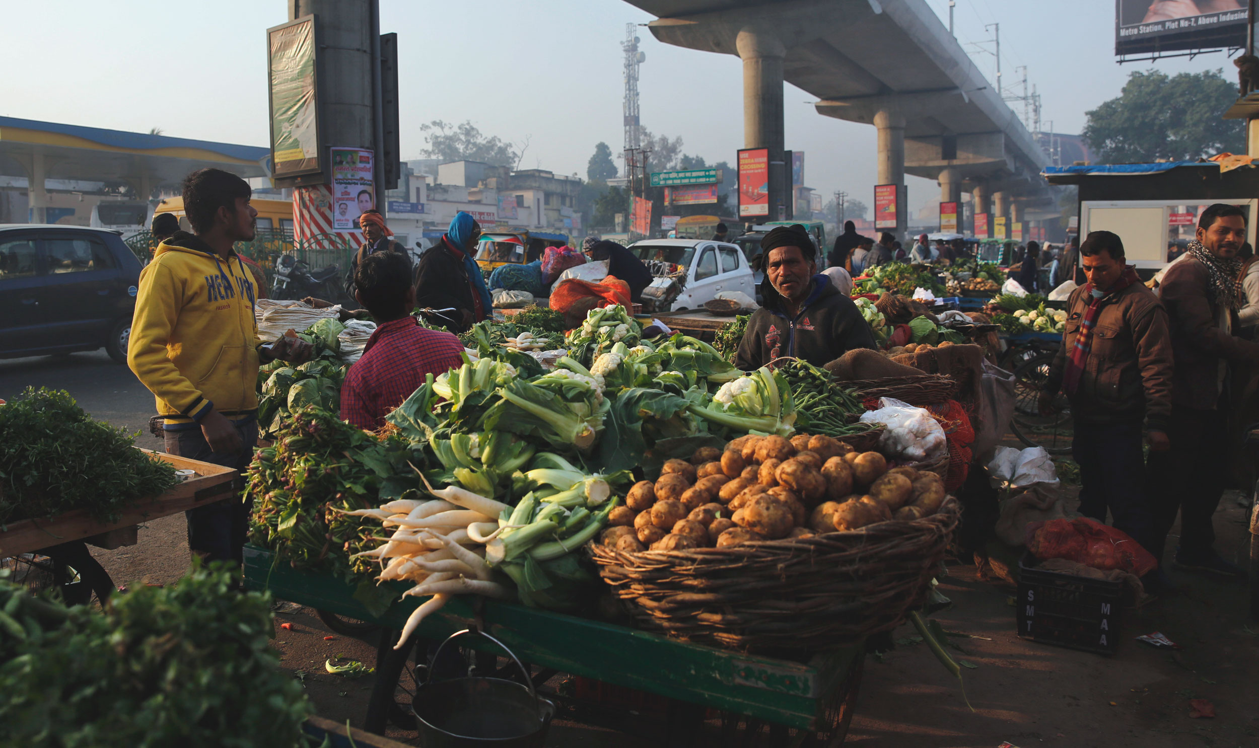 People buy vegetables at a whole sale market in Lucknow on Monday.