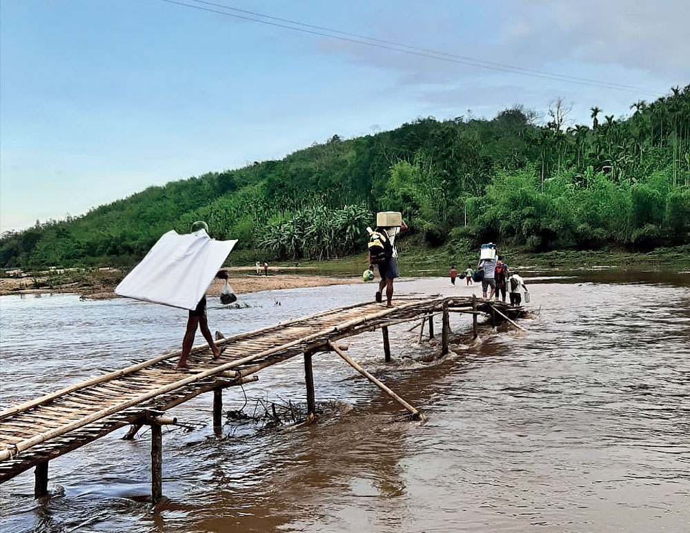 Poll officials crossing a bamboo bridge at Jongmegr across the Simsang in Garo hills