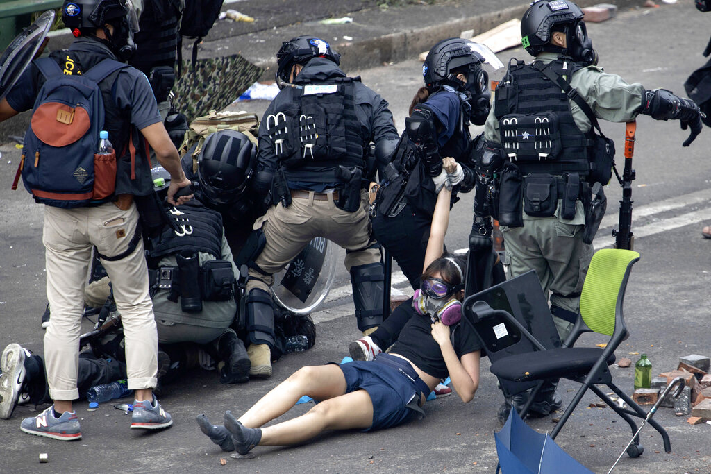 Hong Kong Police in riot gear drag a protester who was trying to flee from the Polytechnic University in Hong Kong, Monday, November 18, 2019