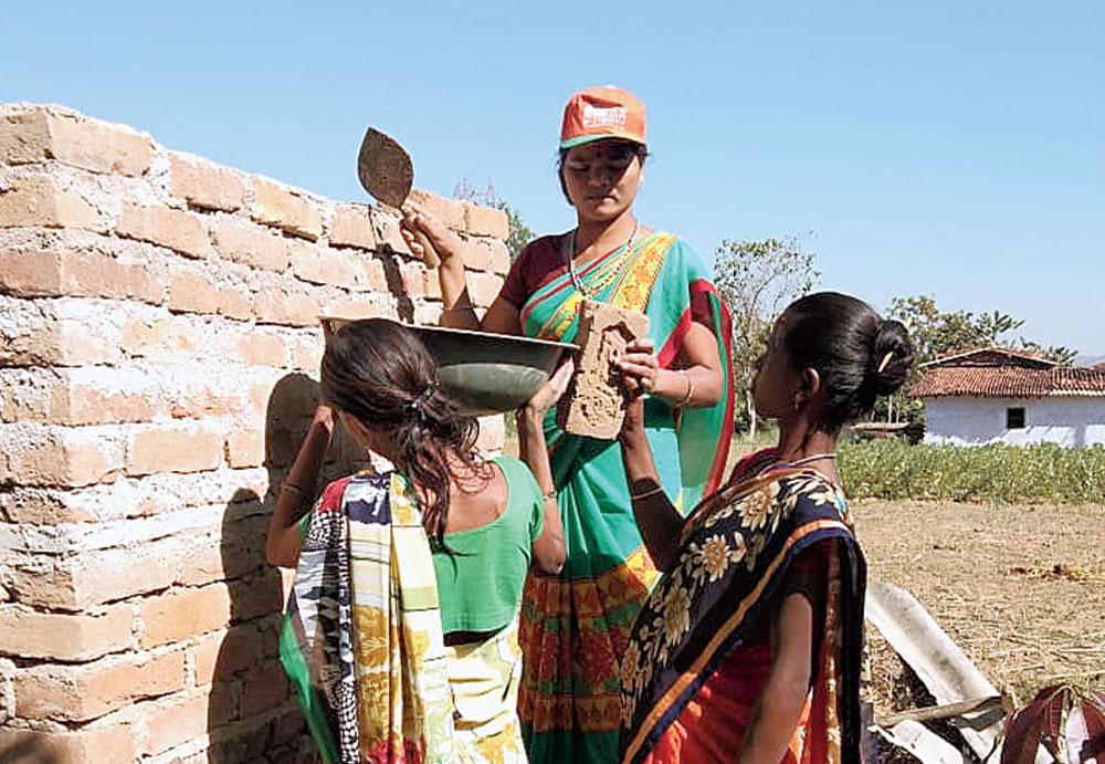 Role Model: Sunita Devi (wearing a cap) constructs a toilet in Latehar in September last year.