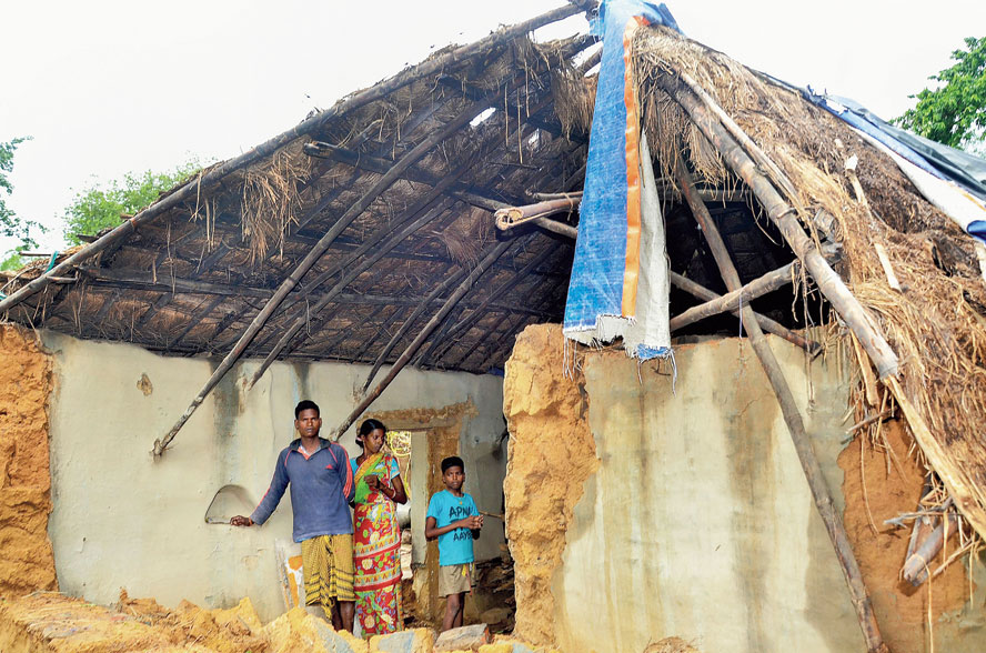 Members of a family at their house damaged in the cyclone at Kharagpur in West Midnapore district.