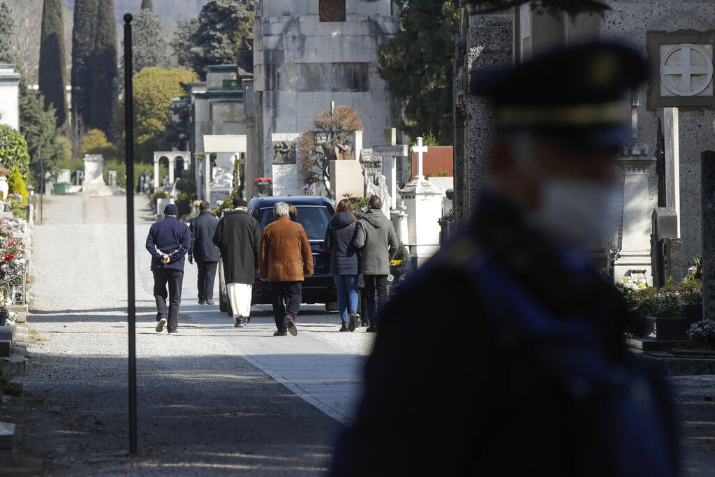 Relatives walk behind a hearse carrying a coffin inside the Monumentale cemetery, in Bergamo, on Tuesday.