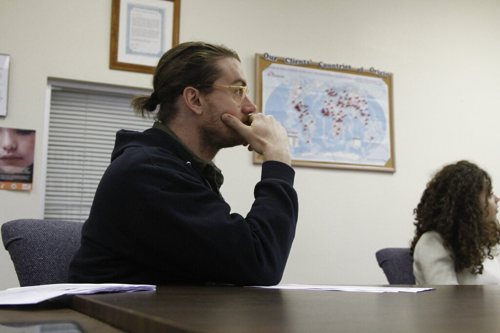 In this November 12, 2019, photo, attorney Nicholas Palazzo watches a presentation by a coworker at Las Americas Immigrant Advocacy Center, in El Paso, Texas. Pushpins on the map behind him mark the homelands of the center's clients. Palazzo is one of about a dozen pro-bono lawyers in El Paso serving a population of 10,000 asylum seekers stuck in legal limbo in neighboring Ciudad Juarez, Mexico.