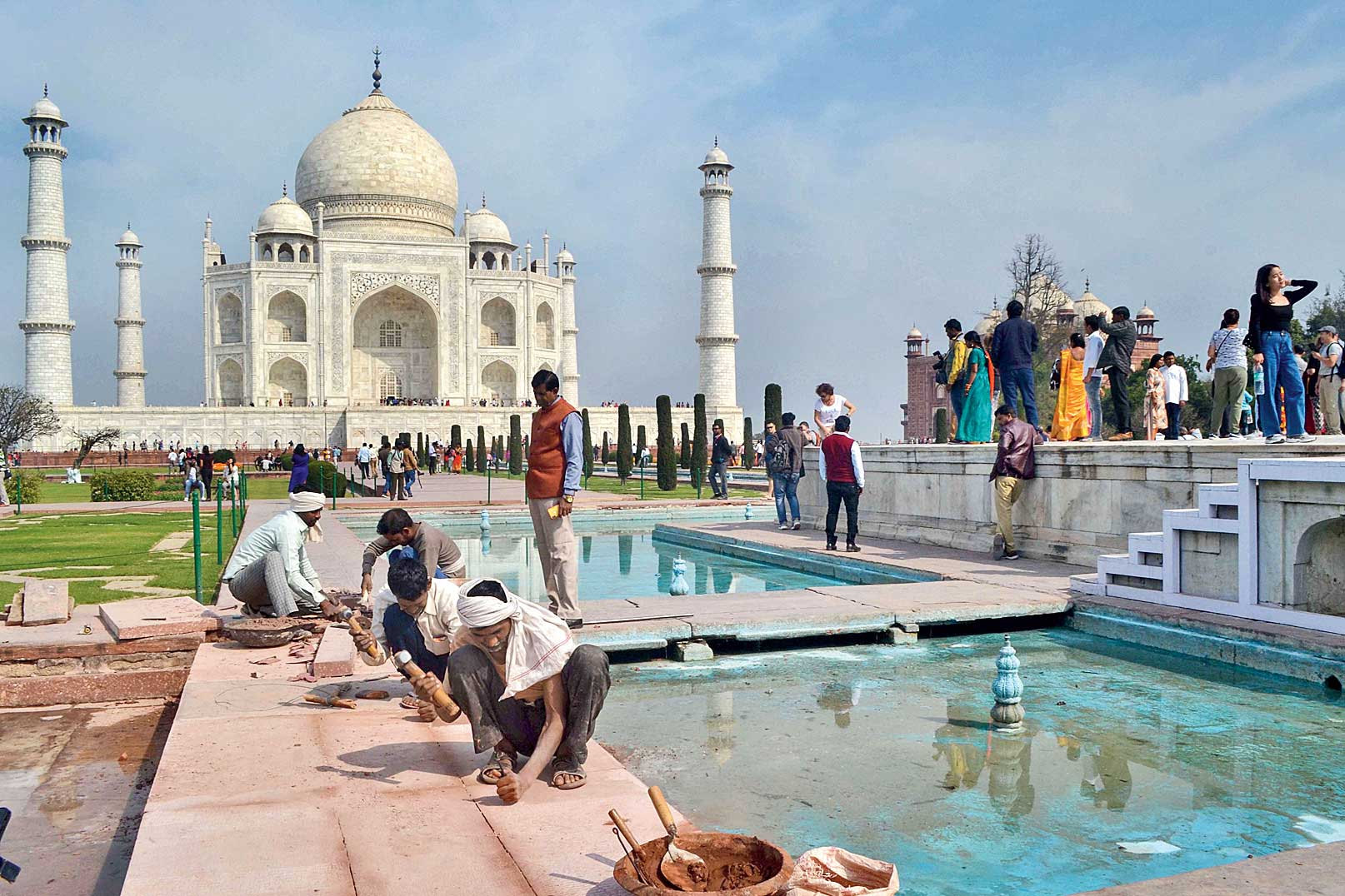 Workers fix tiles near the fountains at the Taj Mahal on Thursday, ahead of US President Donald Trump's visit.