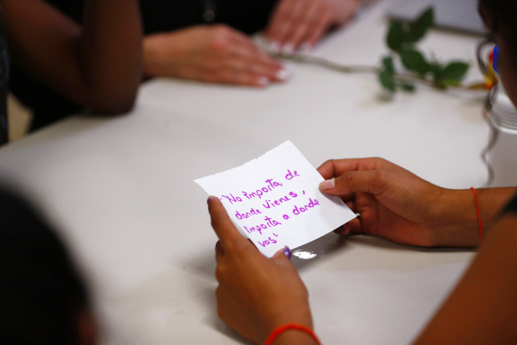 "In this September 24, 2019, photo, a migrant girl in US government custody holds a card that says, in Spanish, ""It doesn't matter where you come from, it matters where you are going,"" during a lesson on reproductive health and self esteem in Lake Worth, Florida."