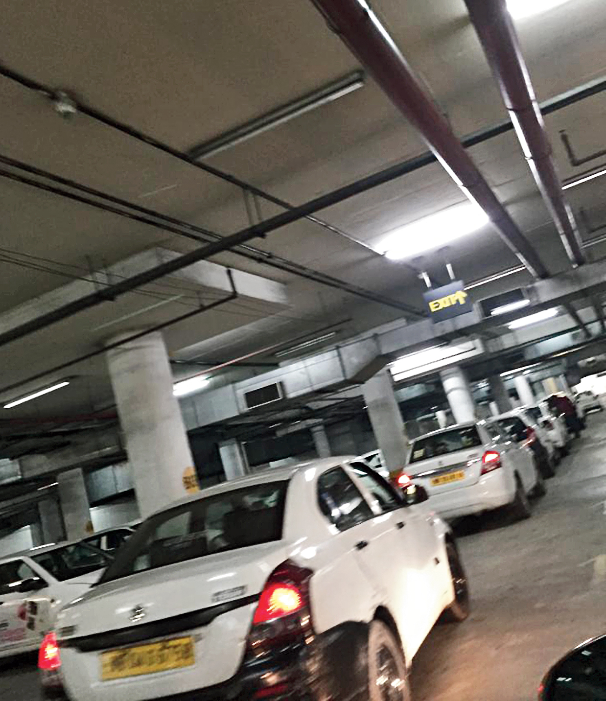 A long queue of cars inside the parking lot on their way to the arrival area of the city airport