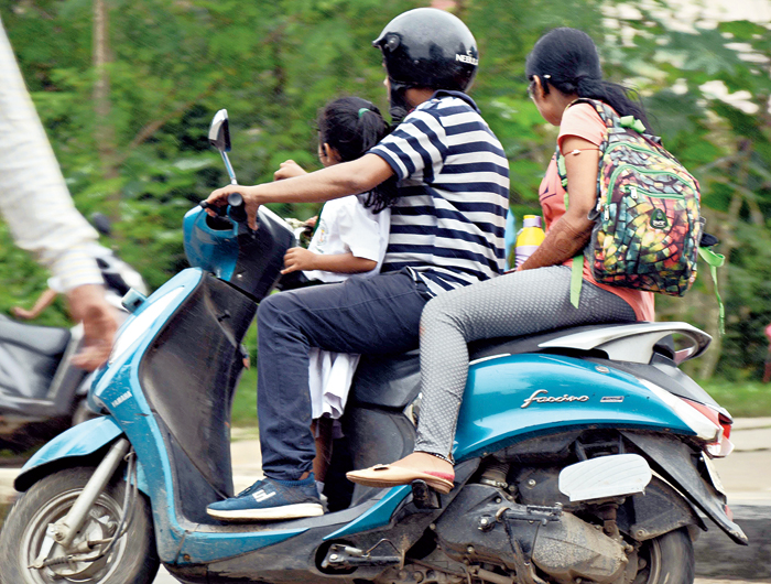 A family of three on a bike at Karam Toli Chowk in Ranchi on Wednesday
